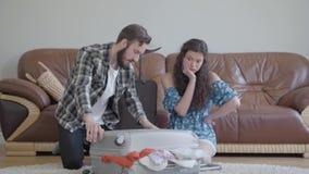 Nerv?ser Mann und Frau, die zu Hause auf dem Boden vor dem ledernen Sofa, versuchend, einen Koffer vor Reise zu verpacken sitzt stock footage
