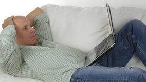 Nervöser und enttäuschter Mann, der auf der Couch schaut gesorgt zu einem Laptop liegt stockbild