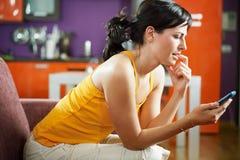 Nervöses Frauenholding-Mobiltelefon Stockbild