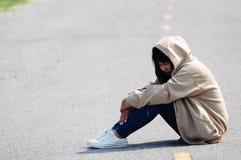 Nervöses Mädchen, das auf der Straße sitzt lizenzfreies stockfoto