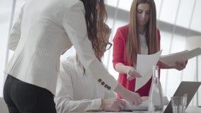 Nerv?ser Mann des Portr?ts, der im modernen B?ro mit netbook am Tisch sammelt Dokumente die zwei weibliche Kollegen sitzt stock footage