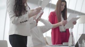 Nerv?ser Mann des Portr?ts, der im modernen B?ro mit netbook am Tisch sammelt Dokumente die zwei weibliche Kollegen sitzt stock video