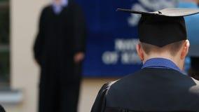 Nervioso graduado del varón antes de caminar en etapa para recibir el diploma de la universidad almacen de metraje de vídeo
