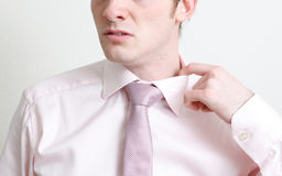 Nervous. A nervous business man pulling his collar royalty free stock image