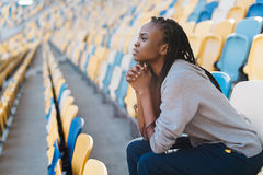 The nervous afro-american teenager is observing the match on the stadium. Close-up side portrait. Royalty Free Stock Image