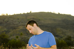Nervous agitated man outside. Man debating what to do next looking down and to the side with a hill in the background at sunset. Nervous agitated man playing Stock Photos