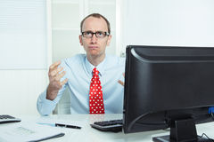 Nervous, annoyed and aggressive businessman sitting at desk in r Stock Photo