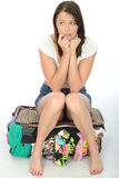 Nervous Anxious Attractive Young Woman Sitting on an Overflowing Suitcase. Nervous Scared Anxious Attractive Young Woman Sitting on an overflowing Suitcase with Royalty Free Stock Photos