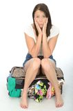 Nervous Anxious Scared Young Woman Sitting on an Overflowing Suitcase. Nervous Scared Anxious Young Woman Sitting on an overflowing Suitcase with clothes Stock Photo
