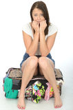 Nervous Anxious Young Woman Sitting on an Overflowing Suitcase Looking Worried Royalty Free Stock Image