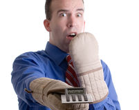 Nervous Banker. Concept image of a nervous banker holding onto his investment with oven mitts, isolated against a white background Stock Image