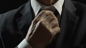 Nervous billionaire adjusting tie at police station, financial crime and bribery. Stock footage stock footage