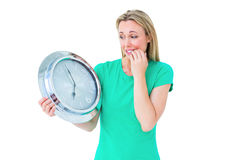 Nervous blonde in casual clothes holding clock Royalty Free Stock Photography
