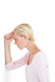 Nervous blonde woman leaning against the wall Stock Photo
