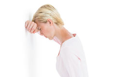 Nervous blonde woman leaning against the wall. On white background Stock Image