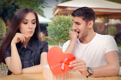Nervous Boyfriend presenting his Gift to his Picky Girlfriend Stock Images