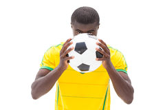 Nervous brazilian football fan hiding behind ball Stock Photo