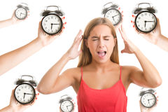 Nervous Breakdown. Woman suffering from a nervous breakdown, holding her hands to her head, with alarm clocks around her, isolated in white royalty free stock photo