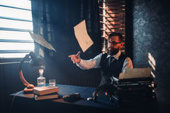 Nervous breakdown, writer throws handwritten text. Nervous breakdown, the writer throws handwritten text sitting at the table with retro typewriter, feather Royalty Free Stock Images