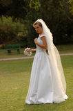 Nervous bride. A beautiful caucasian young bride with nervous expression in her face wearing her white wedding dress and long veil walking with doubts in the stock image