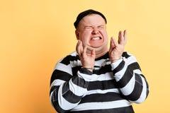 Nervous burglar in panic, shouting , screaming. Nervous burglar with raised hands wearing striped clothes in panic, shouting , screaming, isolated yellow stock photography