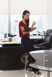 Nervous business woman with anti stress ball holds tablet. Office worker leaning on desk. The woman reads an email on tablet computer and holds an anti-stress Stock Image