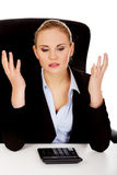 Nervous business woman count on the calculator beahind the desk Royalty Free Stock Photo