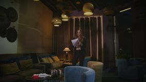 Nervous business woman reading documents in office lounge at night. Upset woman working with papers in hotel lobby at evening. Tired businesswoman working late stock video