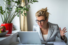 Nervous business woman screaming loudly at her laptop in office. Stock Photography