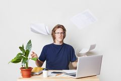 Nervous businessman being tired of paper work throws documents in air, wants to have rest, has furious expression. Young busy male royalty free stock photos