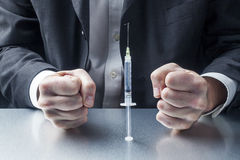 Nervous businessman in front of needle full of vaccine or drugs Stock Photo