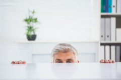 Nervous businessman peeking over desk Royalty Free Stock Photos