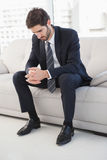 Nervous businessman sitting on couch Stock Photo