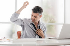 Nervous businessman sweating. Nervous businessman working in the office, he is sweating and checking his armpits Royalty Free Stock Images