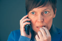 Nervous businesswoman bites fingernails during telephone convers. Ation on mobile phone Royalty Free Stock Photography
