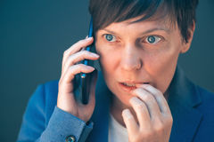 Nervous businesswoman bites fingernails during telephone convers. Ation on mobile phone Stock Image