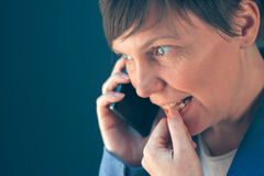 Nervous businesswoman bites fingernails during telephone convers Royalty Free Stock Photography