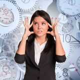 Nervous businesswoman with clocks Royalty Free Stock Photography