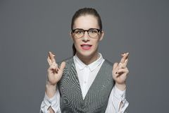 A nervous businesswoman with crossed fingers royalty free stock image