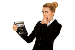 Nervous businesswoman looking at calculator Royalty Free Stock Images