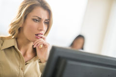 Nervous Businesswoman Looking At Computer. Close-up of nervous young businesswoman looking at computer with colleague in background Stock Photos
