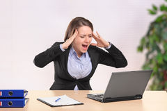 Nervous businesswoman yelling to a laptop. A nervous young businesswoman yelling to a laptop in the office Royalty Free Stock Photo