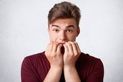 Nervous Caucasian male bites finger nails and feels embarrassed before important event, dressed in casual outfit, isolated over wh royalty free stock photo