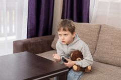 Nervous child sitting on the sofa and watching tv Royalty Free Stock Image