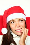 Nervous christmas woman with stress. Christmas woman with santa hat nervous biting nails. Beautiful mixed asian / caucasian model Royalty Free Stock Image