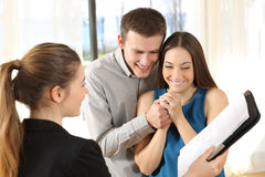 Nervous couple searching a new house. Real estate agent showing a new house plan to a nervous couple Royalty Free Stock Images