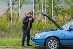 Nervous driver calls to the help desk by phone Royalty Free Stock Photo