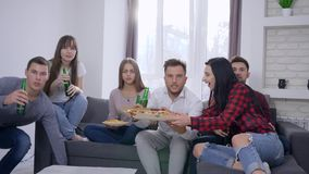Nervous fans attractive young people are watching match on TV, friends brings beer and pizza for celebrating success at stock footage