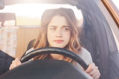 Nervous female driver sits at wheel, has worried expression as afraids to drive car by herself for first time. Frightened woman ha. S car accident on road stock photography
