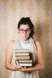 Nervous female student with books. Nervous female student holding a pile of books. Upset woman ready for studying Stock Photo